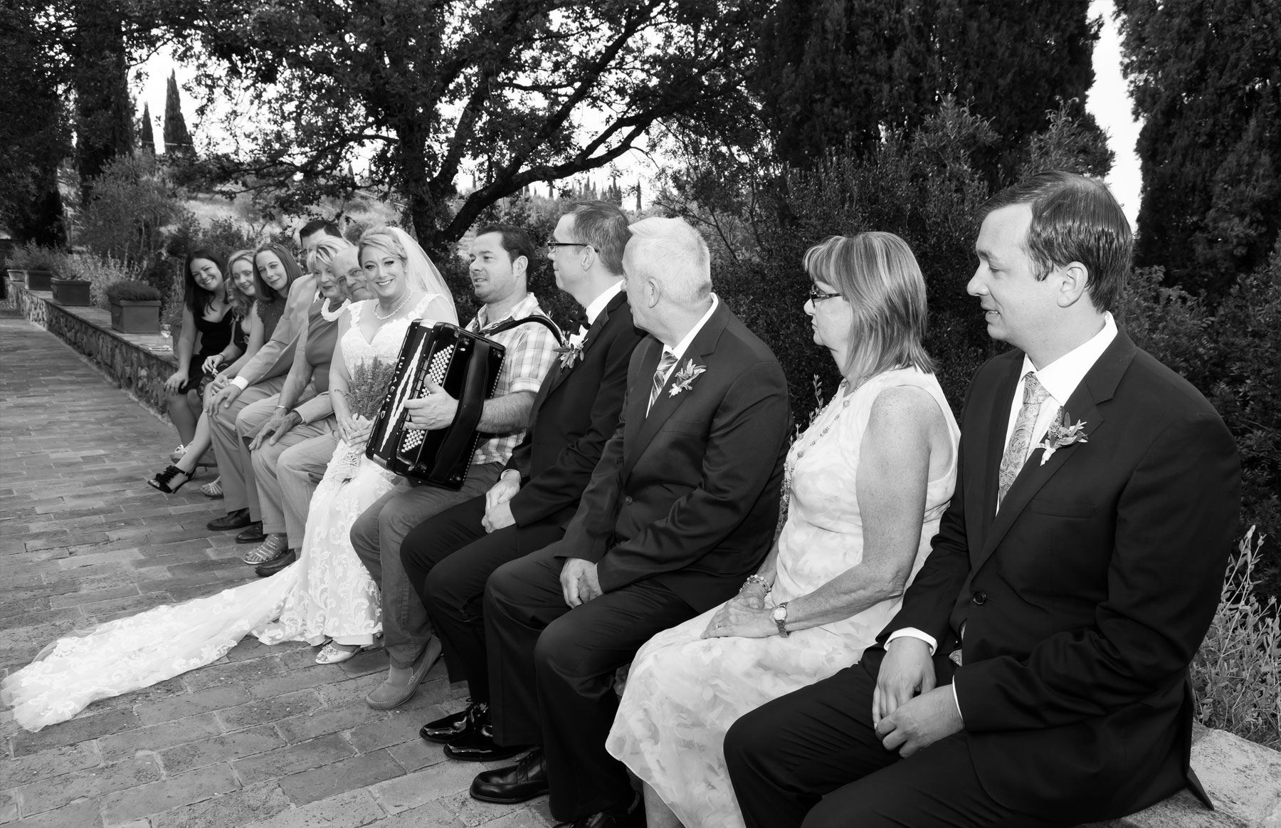 Wedding party sitting on wall with acordian player