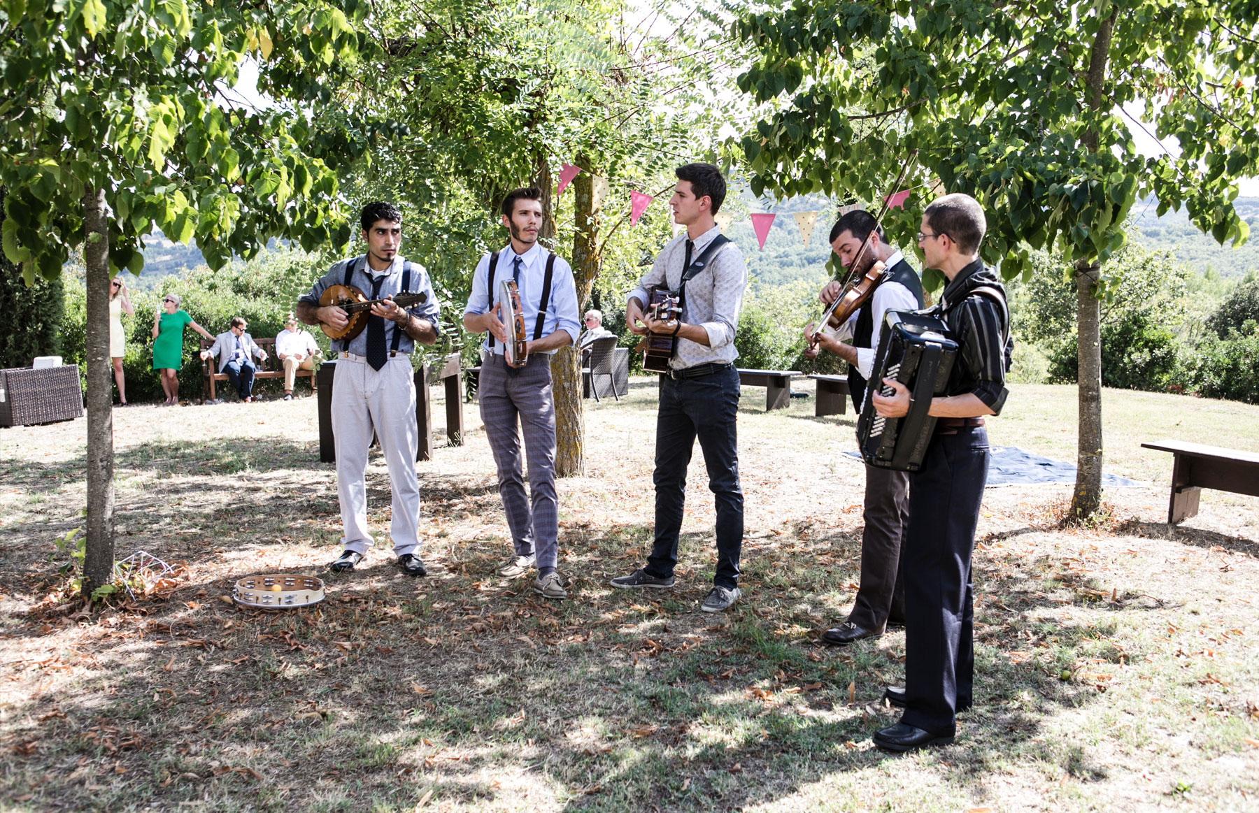 5 musicians playing folk instruments in gardens