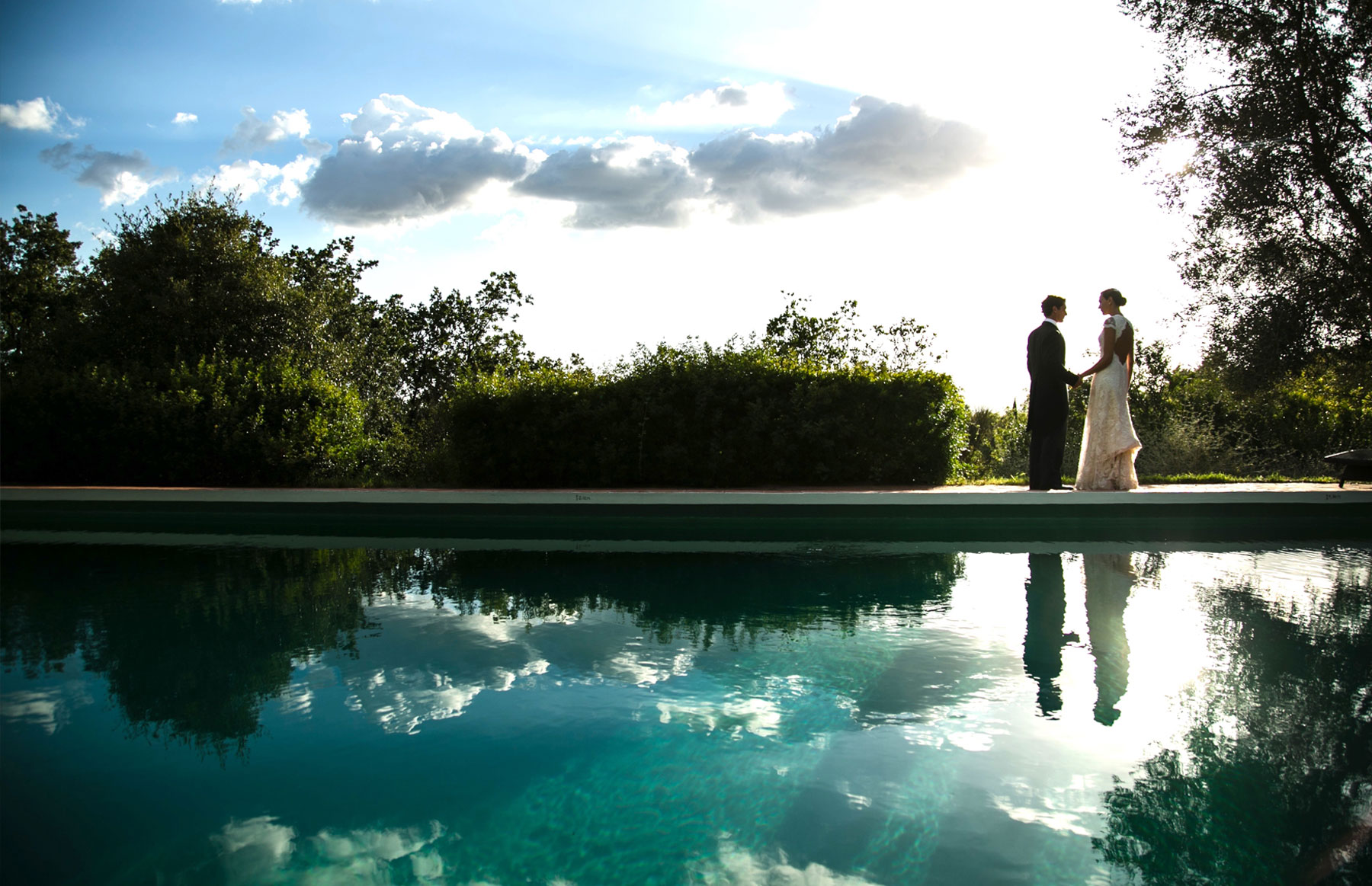 man and woman in wedding outfits standing by pool